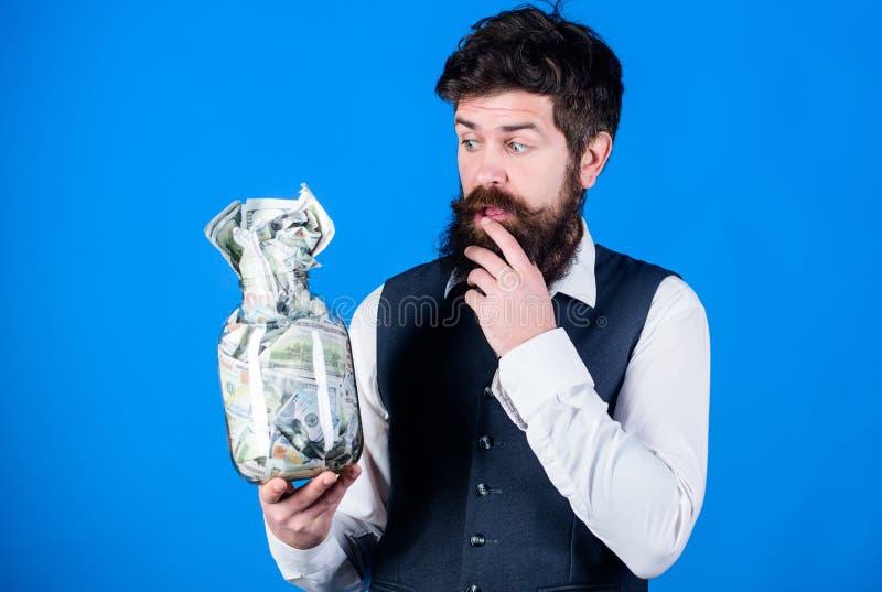 采取金钱挣在他的事务的金钱 有胡子的人认为投资金钱在起始的事务 商人藏品 免版税库存图片