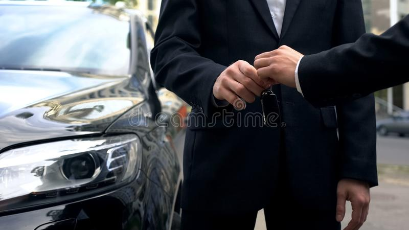 采取钥匙的商人对昂贵的自动,成功的汽车购买交易 免版税库存照片