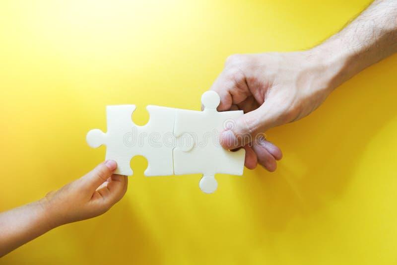 采取难题的片断儿童和父亲手 免版税库存图片
