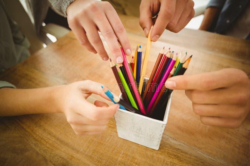 采取颜色铅笔的播种的手特写镜头  图库摄影