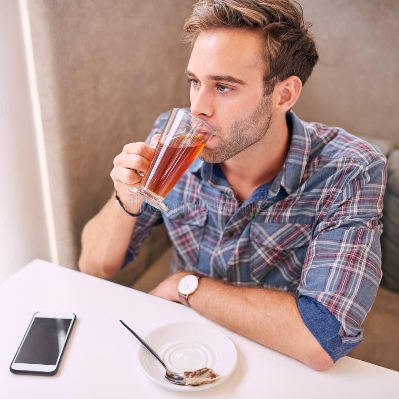 采取饮者她的在咖啡馆的茶的好loking的人 免版税库存照片