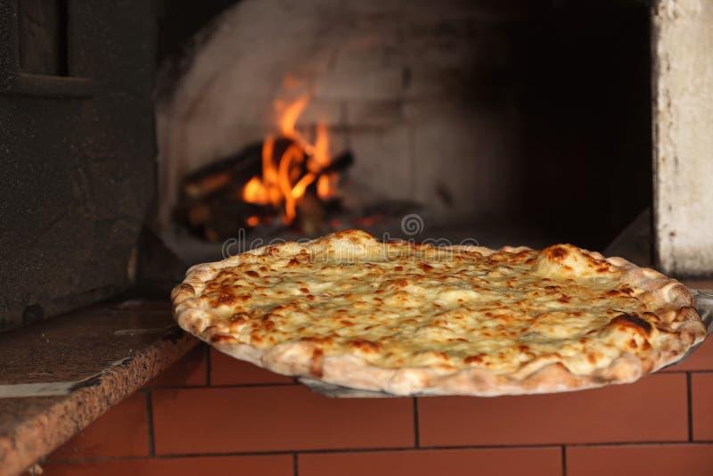 采取鲜美比萨在烤箱外面在厨房里 免版税库存照片