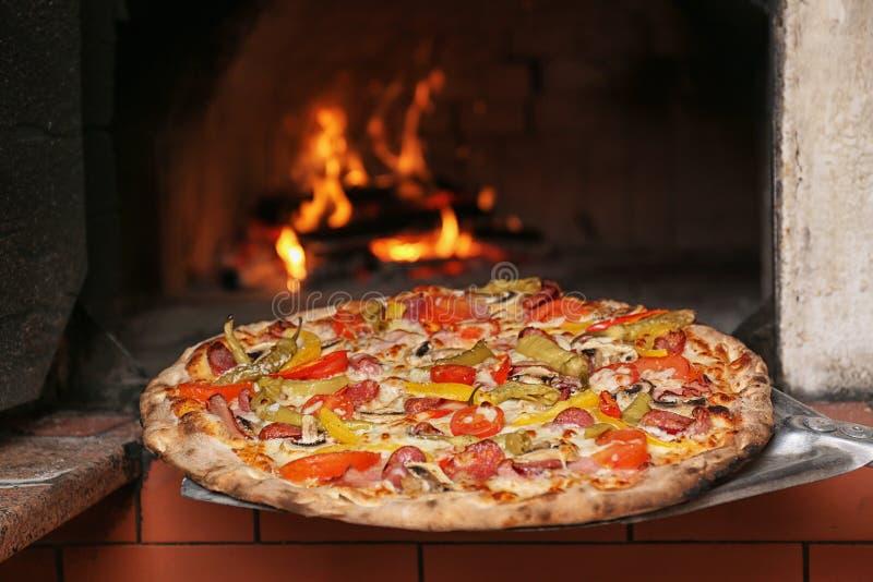 采取鲜美比萨在烤箱外面在餐馆 库存照片