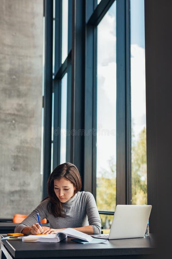 采取从书的学生笔记在图书馆 免版税库存照片