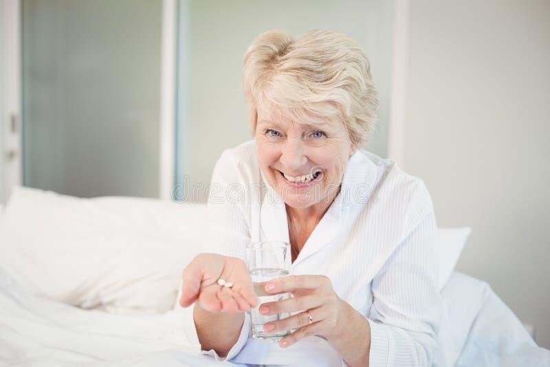 采取医学的愉快的资深妇女 库存图片