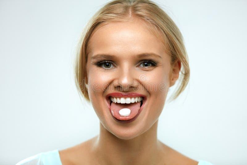 采取医学的美丽的微笑的妇女,拿着在舌头的药片 免版税库存照片