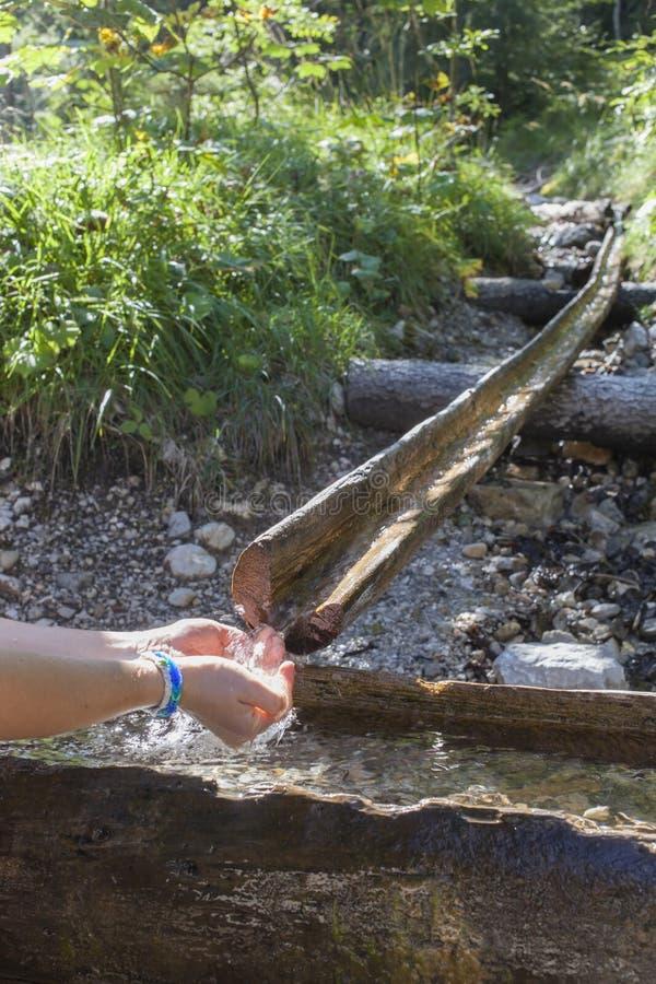 采取从山小河的远足者水 图库摄影