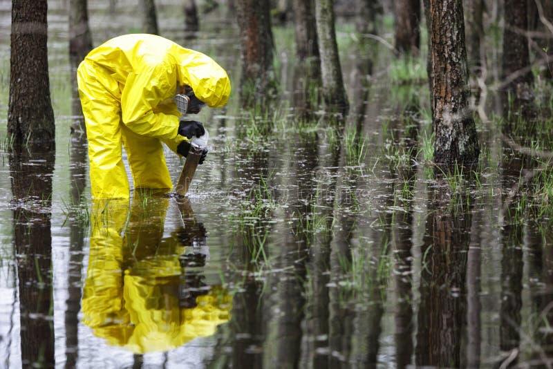 采取水的样品技术员到在洪水的容器沾染了区域 免版税库存图片