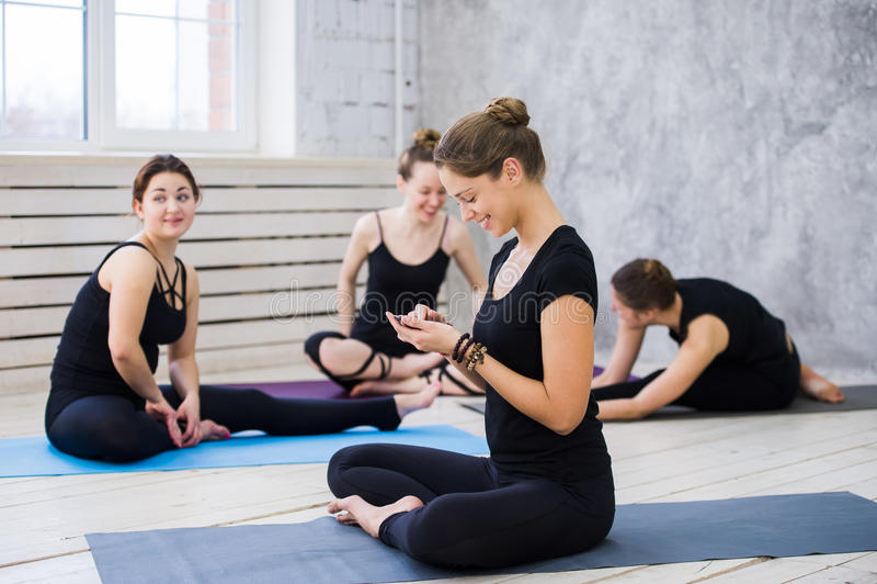 采取从他们的锻炼的一个断裂和与手机的逗人喜爱的愉快的舞蹈家或瑜伽类社会网络 免版税库存图片