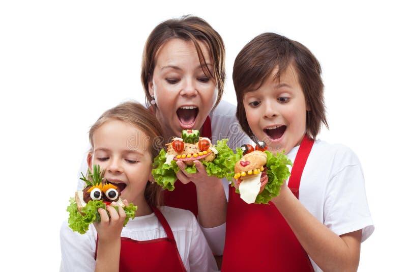采取滑稽的生物三明治的叮咬孩子和妇女 库存照片