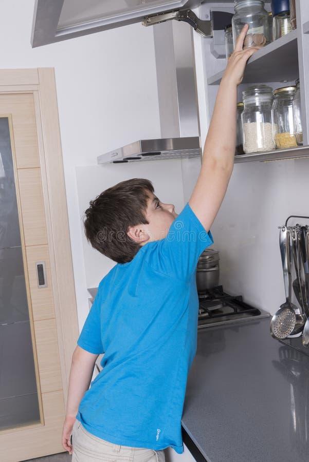 采取从高厨柜的年轻男孩糖果 库存照片