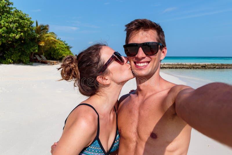 采取selfie、热带海岛和清楚的大海的愉快的年轻夫妇作为背景 亲吻他的男朋友的女孩 库存照片