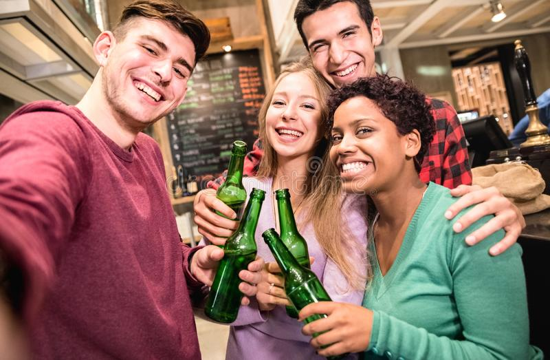 采取selfie和喝啤酒的多种族朋友在花梢啤酒厂客栈 免版税库存照片