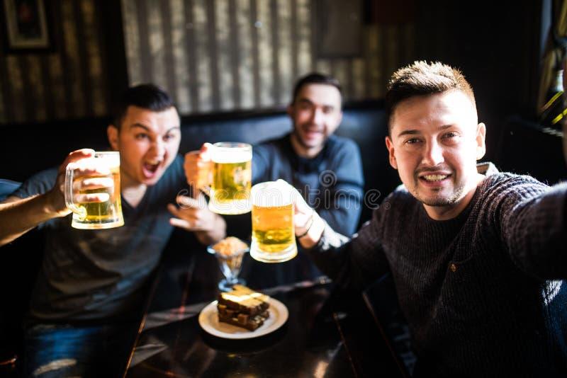 采取selfie和喝啤酒的愉快的男性朋友在酒吧或客栈 免版税库存照片