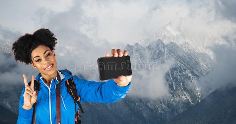 采取selfie和打手势和平标志的行家,当站立反对积雪覆盖的山时 库存图片