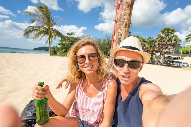 采取selfie在海滩-旅行生活方式概念的愉快的夫妇 免版税库存图片