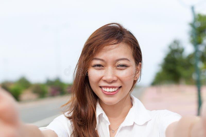 采取Selfie照片美好的愉快的微笑的妇女图象的亚裔女孩 库存照片