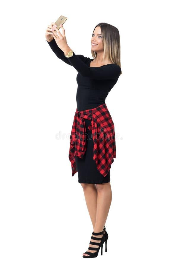 采取selfie用两只手的微笑的年轻俏丽的妇女看电话 免版税库存图片