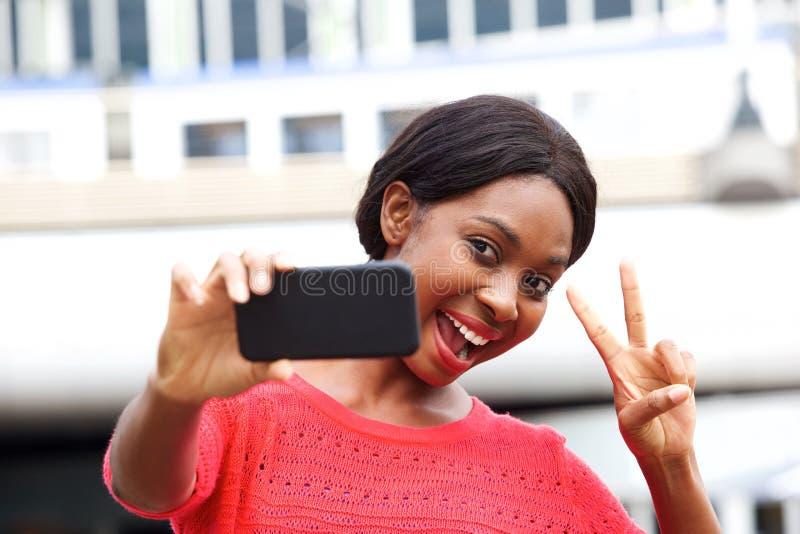 采取selfie用和平手的愉快的年轻黑人妇女在城市签字 图库摄影