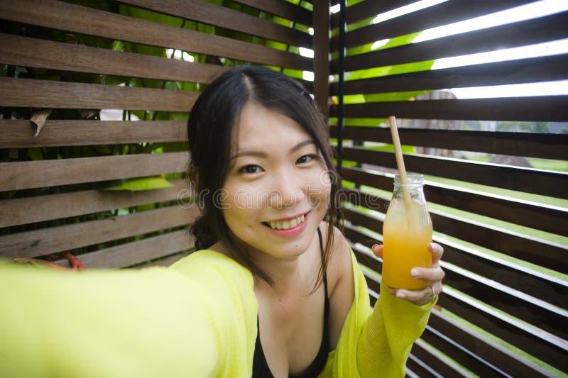 采取selfie画象照片户外喝的年轻美丽和愉快的亚裔美国人学生女孩生活方式画象橙色 库存图片