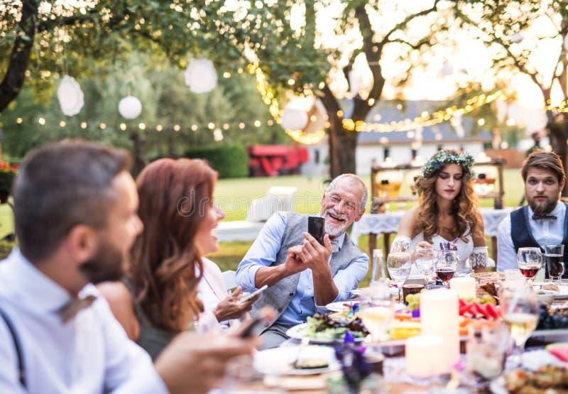 采取selfie的一名老人在结婚宴会外面在后院 免版税图库摄影