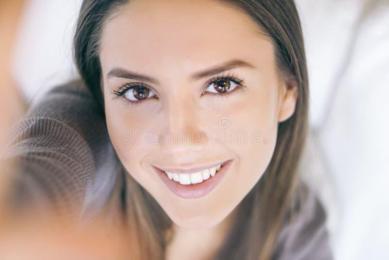 采取selfie的一美丽的年轻女人的接近的画象,当在家时放松在沙发 库存照片