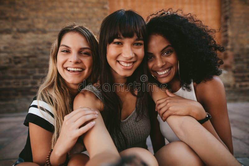 采取selfie的三个美丽的微笑的女朋友 免版税库存图片