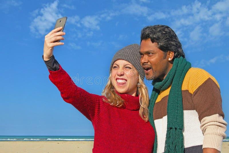 采取selfie的不同种族的夫妇使用智能手机 免版税库存图片