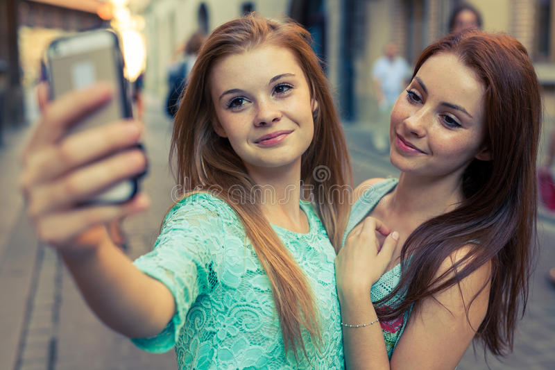采取selfie的两个俏丽的女孩 都市的背景 我们爱selfie 库存图片