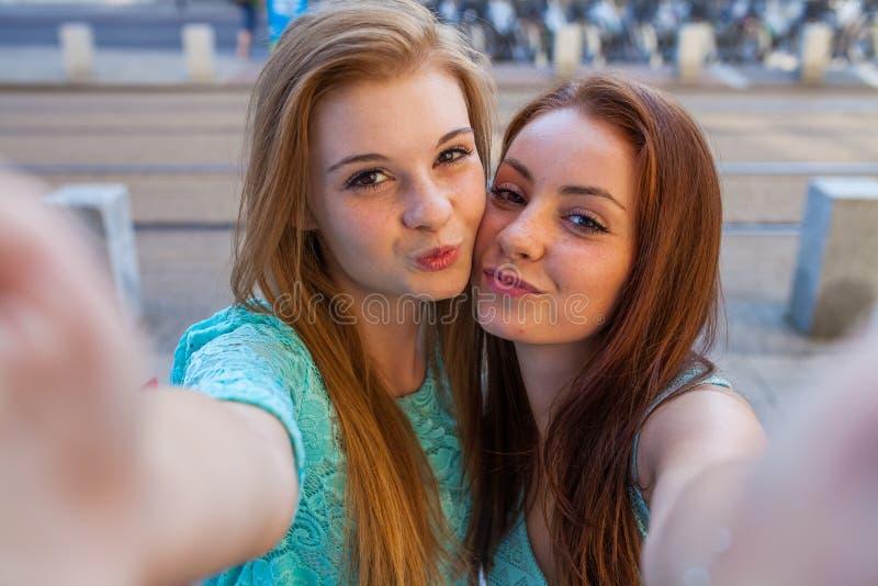 采取selfie的两个俏丽的女孩 都市的背景 我们爱selfie 库存照片