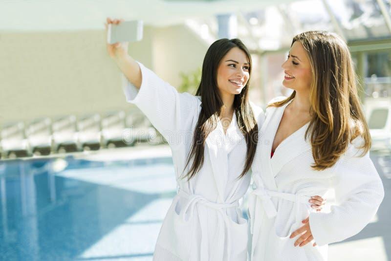采取selfie的两个可爱的夫人在游泳池旁边 库存图片