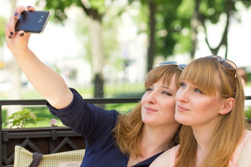 采取selfie的两个孪生女孩在餐馆 免版税图库摄影