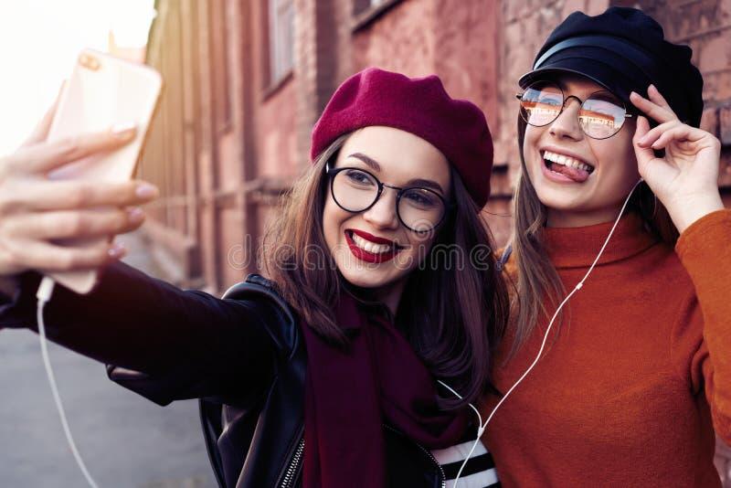 采取selfie的两个快乐的快乐的女孩,当走在获得城市的街道乐趣时 免版税图库摄影