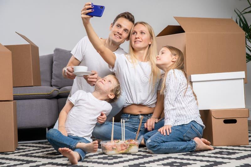 采取selfie的人、孩子和妇女的图象坐在纸板箱中的地板 库存图片