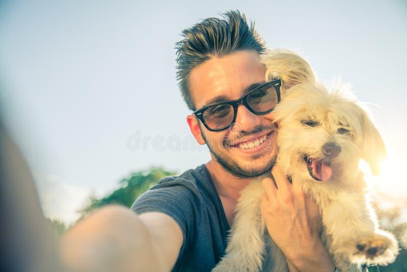 年轻采取selfie的人和他的狗 免版税库存图片