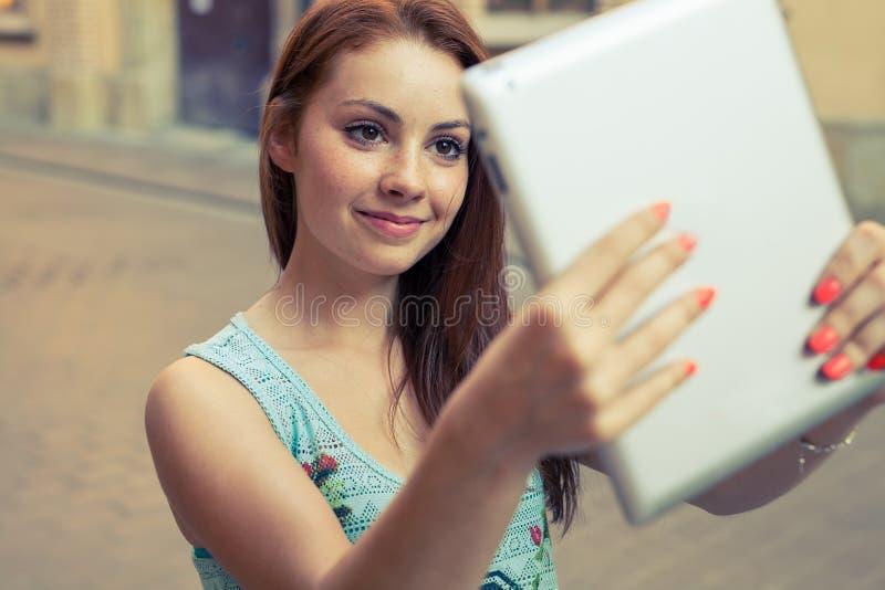 采取selfie的俏丽的女孩 都市的背景 调遣结构树 库存图片