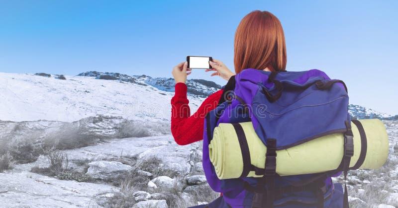 采取selfie的千福年的背包徒步旅行者反对多雪的小山 免版税库存照片