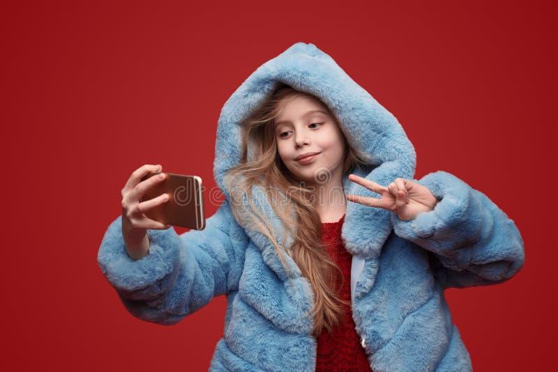 采取selfie的外套的时髦孩子 免版税库存照片