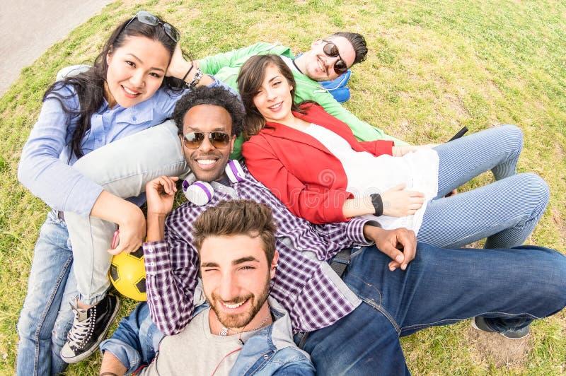 采取selfie的多种族最好的朋友在草甸野餐-与年轻人的愉快的友谊乐趣概念获得的millenials乐趣 库存图片