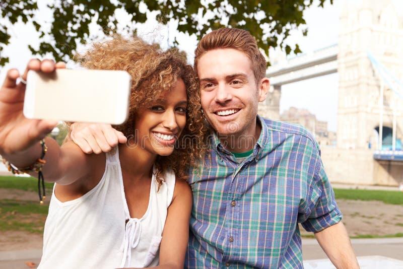采取Selfie的夫妇由塔桥梁在伦敦 免版税图库摄影