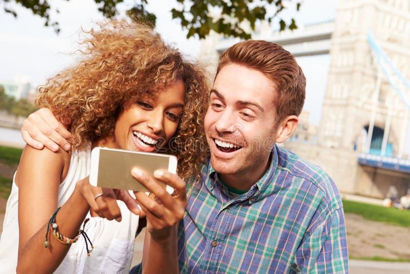采取Selfie的夫妇由塔桥梁在伦敦 库存照片
