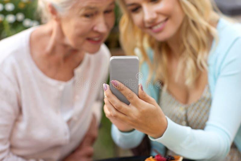 采取selfie的女儿和资深母亲在公园 免版税库存图片