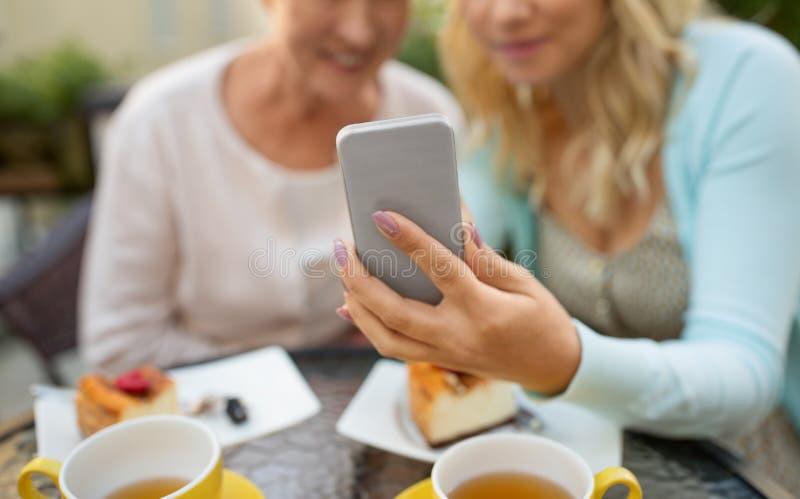采取selfie的女儿和资深母亲在咖啡馆 免版税库存图片