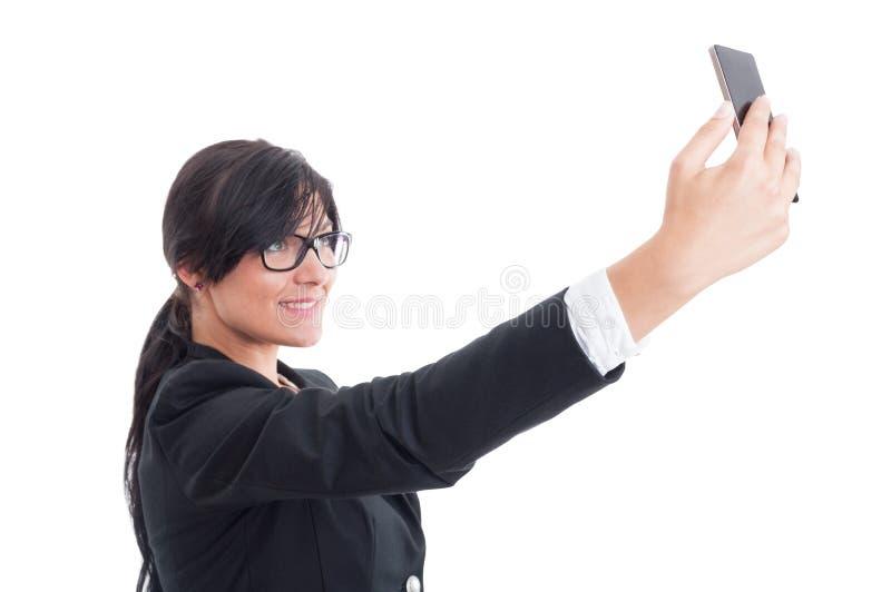 采取selfie的女商人使用智能手机 免版税库存照片