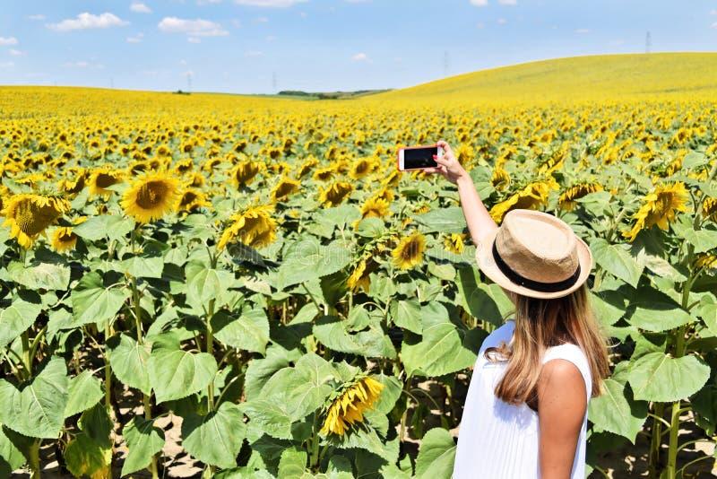 采取selfie的女孩在向日葵农场 图库摄影