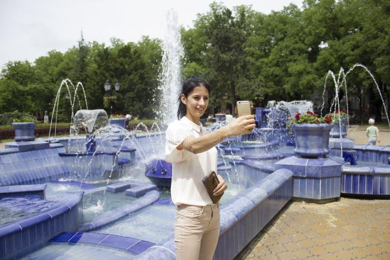 采取selfie的女孩在喷泉旁边 免版税库存照片