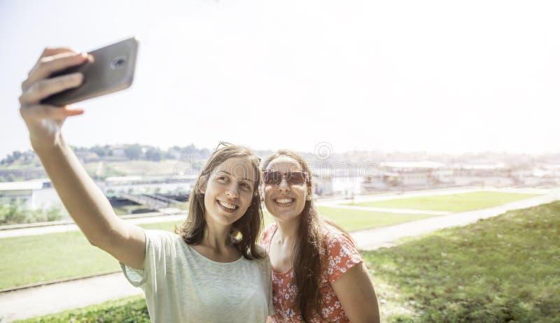 采取selfie的女朋友一起有乐趣现代愉快妇女友谊生活方式女性的最好的朋友的户外概念 库存图片