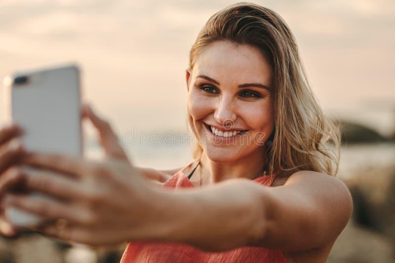 采取selfie的妇女站立在海滩 免版税库存照片