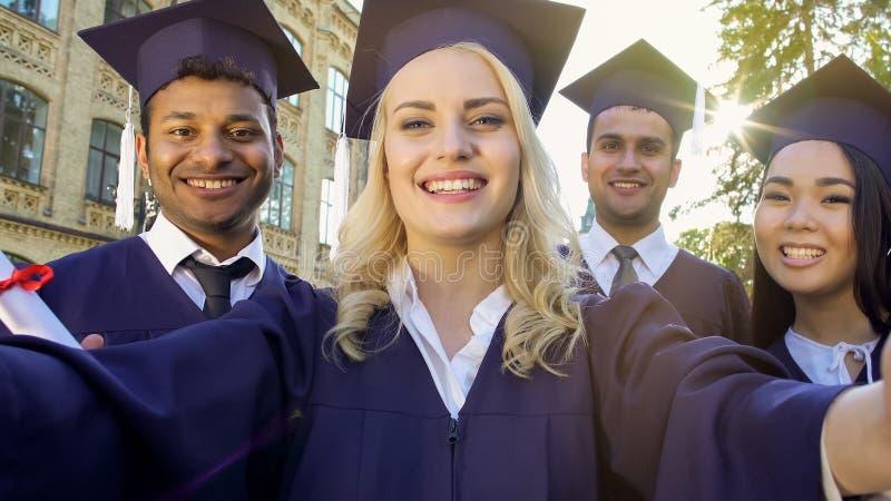 采取selfie的学术礼服的愉快的同学在毕业典礼举行日,成就 图库摄影