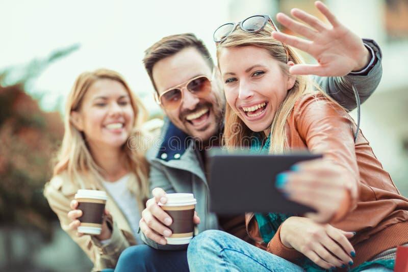 采取selfie的小组微笑的朋友 库存图片